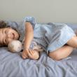 усмихнато момиченце лежи на леглото и гушка плюшената си кукла-бебе